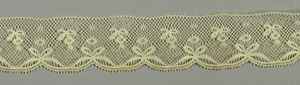 Edging lace showing a design of bow knots and flowers on diamond mesh; one edge scalloped.