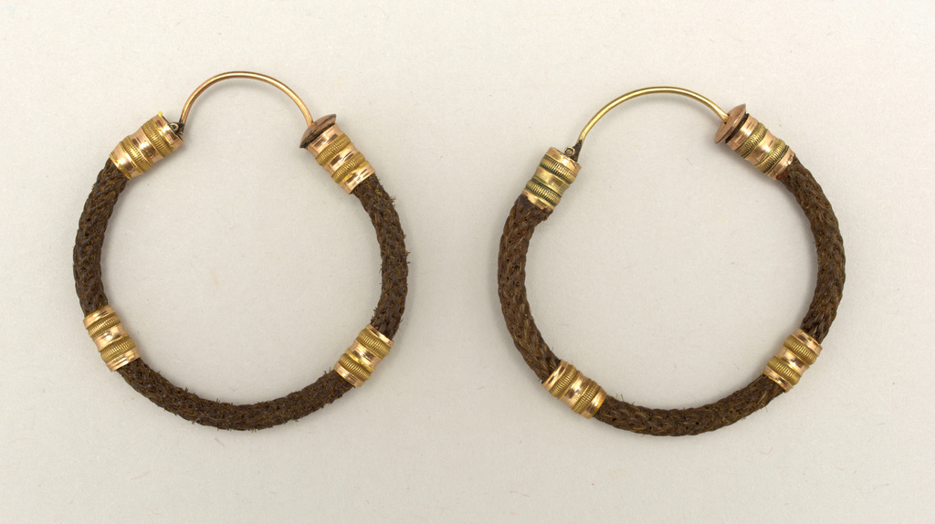 A) and B). Gold hoop with heart and ball ornaments and band of woven human hair.