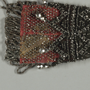 Coral colored silk, fringed and covered evenly with cut steel beads, which form the outer ends of the bag.  The middle, of crocheted black silk, is sewn to the coral portion; triangular lappets of black silk crochet, with cut steel pendants at each triangular point, overlap the coral.  Two cut steel rings control the side closing.