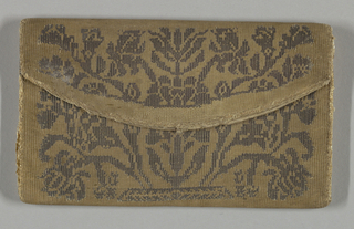 Small envelope-shaped case. Very faded and soiled rose color with a woven design in silver. Symmetrical stylized design of flowers and foliage. Lined with cream white taffeta. Has been edged with very narrow silver braid which remains under one flap.