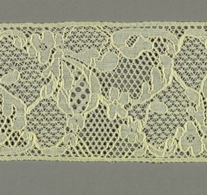 White lace fragment showing abstract fruit-like forms in the manner of the eighteenth century.