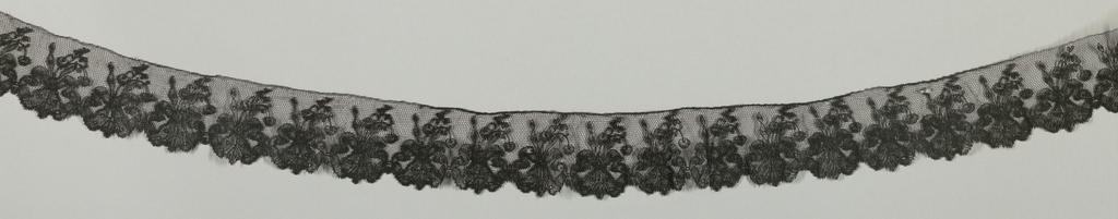 Black Chantilly-type edging lace showing a pattern of floral sprays and bow-knots.