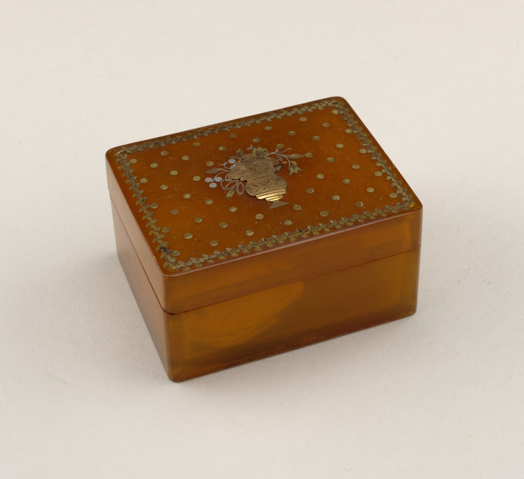 Rectangular amber horn snuff box; on lid: repeated floral motif border around edge, evenly spaced dot pattern across top, decoration of vase with flowers in center with chased gilt-metal.
