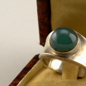 Plain silver band, narrow at bottom, wider at top, surmounted with bezel-set spherical, dark green onyx stone.