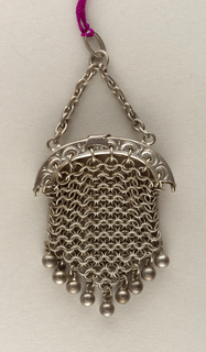 A metal purse made up of linked metal rings hanging from the arched clasp. At the bottom of the purse hangs a row of metal balls.
