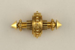 Central cylindrical shaft on horizontal axis; ten smaller cylinders bundled around center and over that a large cylindrical band with beaded border; conical terminals at each end of central shaft and small beaded bands just inside. Back has hinged clasp with hook closure.
