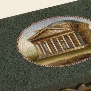 Flat oblong with square corners, hinged at center of heights with scroll outlined thumb-piece. Interior is closed in at perimeter by metal mounts to form rectangular opening with round corners. Oval field on cover with the Pantheon in mosaic of colored stones, with border of fine red dots.