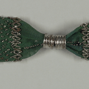 Netted dark green silk ornamented with cut steel beads in a pattern of dots and bands in diamond patterns. Two steel rings control side opening. A fringe of steel beads at one end; a steel bead tassel at the other end.