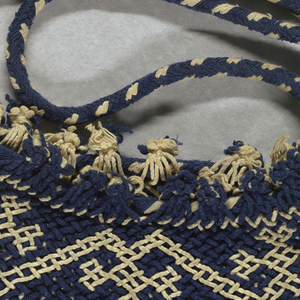 Bag in blue and white double cloth showing a bird perched on a branch in the center field, surrounded by narrow border on three sides in repeat patterns of smaller birds. Top border shows repeated medium-sized birds. Plaited net border with drawstring on top.