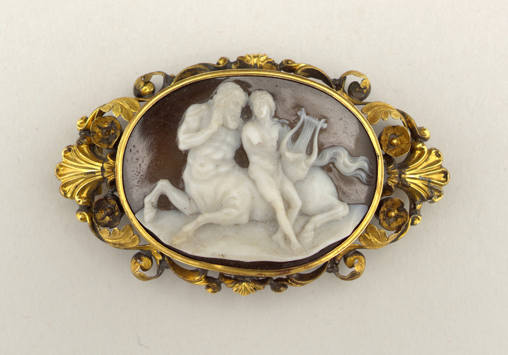 Shell cameo (white on brown) representing Apollo and Chiron, surrounded by a gold frame in design of scrolls with leaves and flowers.