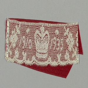 Lace fragment with a slightly scalloped edge and crown with the dates 1910–1935 between small floral sprays. Made at the time of the Jubilee commemorating the 25th anniversary of the accession of George V. Two pieces of red satin ribbon attached to the lace.