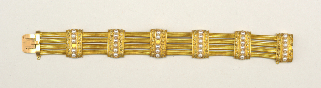 Six bands of gold, each ornamented with six half-pearls and a vine design in colored gold, crossing four flexible strans of gold.  Clasp closing concealed in one band.  Two half pearls and small chain at clasp are missing.