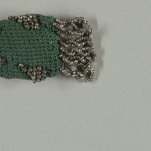 Tightly crocheted dark green silk ornamented with cut steel beads in small geometric pattern.   Two steel rings at closing; at one end, a fringe of steel beads; small faceted drop and tassel at the other.
