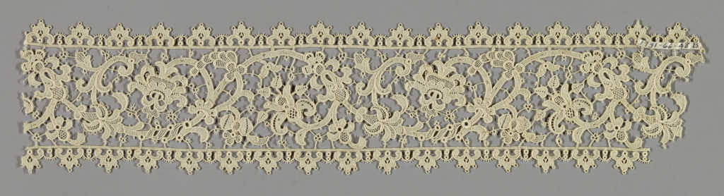 Scalloped bands made in the style of imitation Venetian needle lace has a pattern of scrolling stems with flowers and leaves set between two scalloped edges.