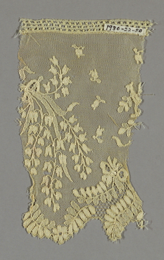 Lace fragment made in imitation of Spanish-style lace with a net ground and a border of leaves and flowers.