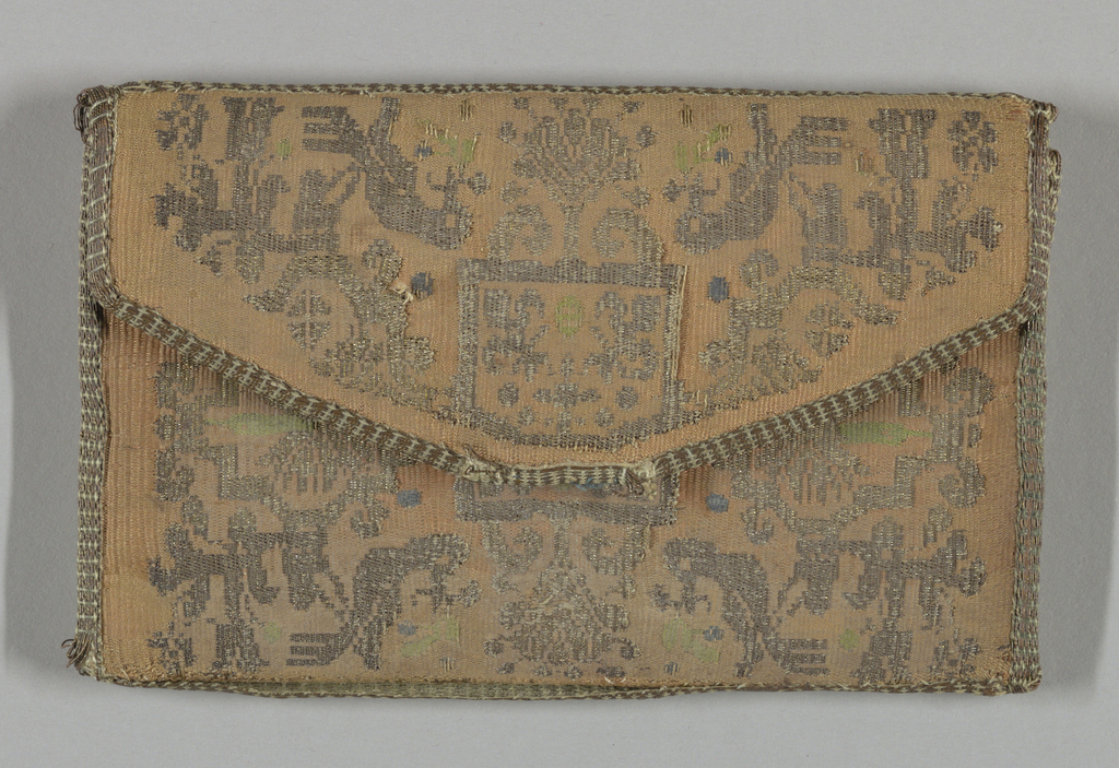Small and flat envelope-shaped pocket book woven in salmon-colored silk, gold and silver thread and small areas of colored silk. Pattern has a square in the center that frames four fleurs-de-lis in the corners. Surrounding area is patterned with birds, medallions and stylized floral forms.