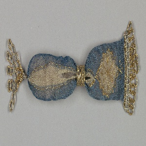 Netting blue silk with asymmetrical area of white silk forming a bar and serrated diamond pattern.  White areas outlined with gold beads; eight-pointed gold bead star within diamond-shaped white area.  Two gold rings with blue floral areas at opening.  A fringe at one end and tassel at other consist of gold beads and beads and twisted wire of silver-colored metal.
