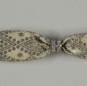 White silk purse ornamented with cut steel beads in zigzag and diamond patterns. Two steel rings with raised ball pattern, control side opening; tassels of steel bars and beads at either end.