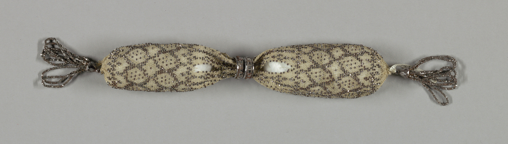 Crocheted white silk ornamented with cut steel beads in overall diamond pattern.  Two steel rings control side opening; tassels of steel beads at either end.
