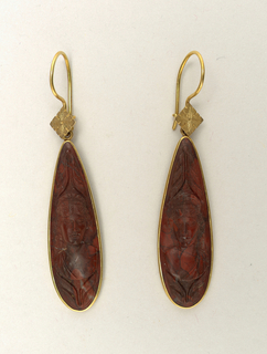 A) and B) Design of small lozenge-shaped plate of gold carved to represent a flower, above a long-oval pendant of red lava carved to represent a woman's head, set in a gold rim.