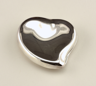 Irregular heart-shaped case with contoured lid; opens clam shell-style to reveal mirror on inside of lid and circular cake of flesh-toned face powder in base. Indented finger grip on rim edge at right near base of heart.