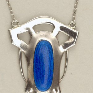 the shield-shaped silver pendant with three cut-out openings at top above a  guilloché blue enamel oval with punched circles below, a baroque pearl drop suspended at the bottom