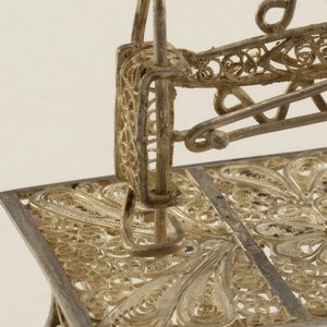 Filigree miniature comprising sewing machine form on rectangular table top with decoration in three panels, on scrolled supports. The working parts consist of a treadle, crank, slotted arm, and needle.
