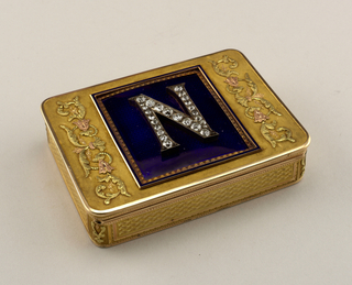 "Box, oblong with rounded corners; gold with bleu de roi enamel plaque on cover with applied ""N"" inlaid with diamonds."