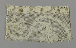 Fragment of Valenciennes lace has a widely swinging serpentine of alternating leaf and five-petal blossom. Border added later. Round mesh.