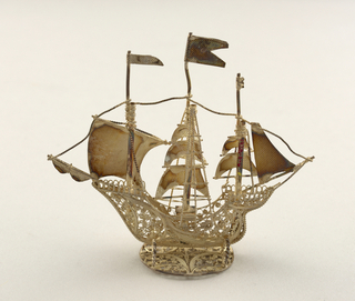 Three masted ship, the foremast carrying the main sail, which bears a cross of pierced silver, with sails and flags of pebbled texture.  Supported by wire spirals on oval filigree stand.
