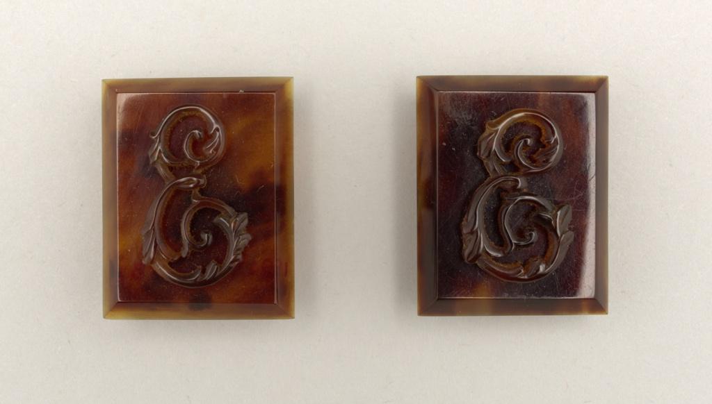 A pair of rectangular tortoiseshell cuff links with ornate 'E' monogram on each link
