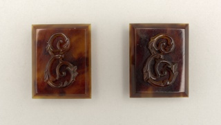 A pair of rectangular tortoiseshell cuff links with ornate 'E' monogram on each link