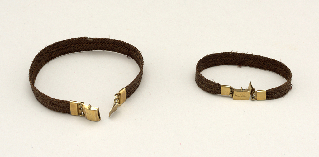 """A) Bracelet composed of a flat band of brown hair with gold clasp marked: """"H. L. Thorn"""". B) Bracelet composed of a flat band of brown hair with gold clasp marked """"E. A. Thorn""""."""