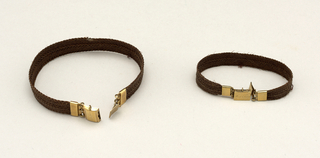 "A) Bracelet composed of a flat band of brown hair with gold clasp marked: ""H. L. Thorn"". B) Bracelet composed of a flat band of brown hair with gold clasp marked ""E. A. Thorn""."