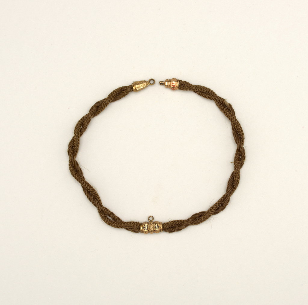 Watch chain made of two strands of human hair (brown) worked in different designs; gold mountings at either end and in center.