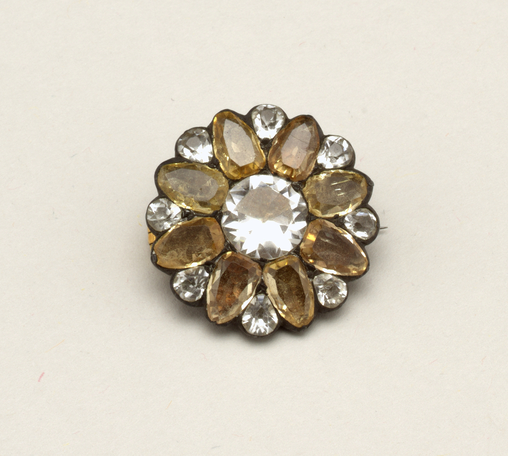 Brooch in the form of a flower with a white center, eight yellow petals and a small white stone set between each two petals.  Pin is a replacement.