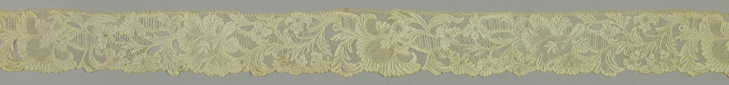Border with striped serpentine band interspersed by floral and foliated forms at intervals.