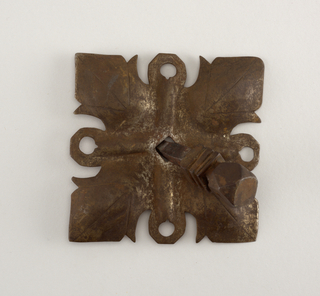 Square type, pierced and embossed with wrought lines. Quadrant leaf design based on old examples; leaves separated by embossed ridges. Nail with square, faceted head above three square collars and a square hank.