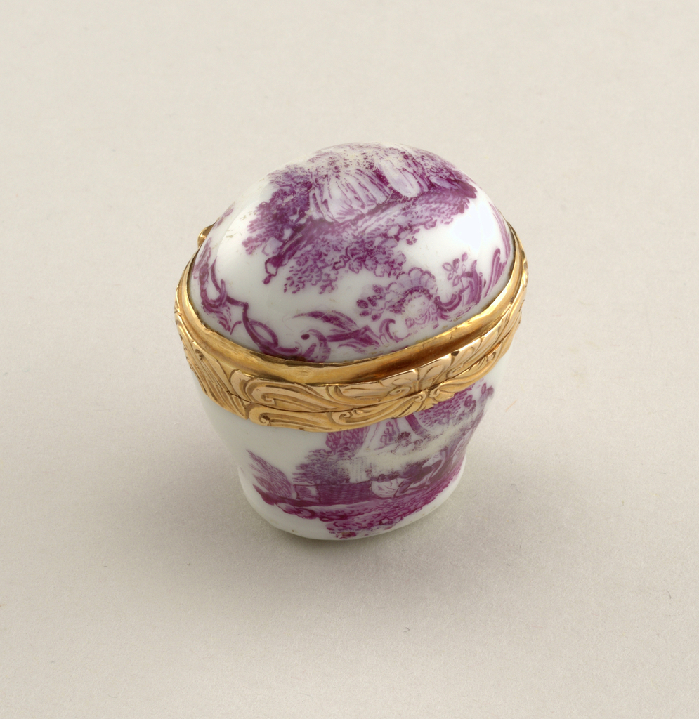 Small white porcelain box with gild metal closure. Decorative scene depicting figures in the outdoors.