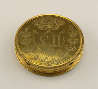 a) Circular box with four holes on sides for cards. On bottom, engraved shield with LII , crowned. Inside the Great Seal of the Austro-Hungarian Empire, surrounded by legends.  b) Cover, with four indentations on sides. Top engraved with Leopold II's arms.