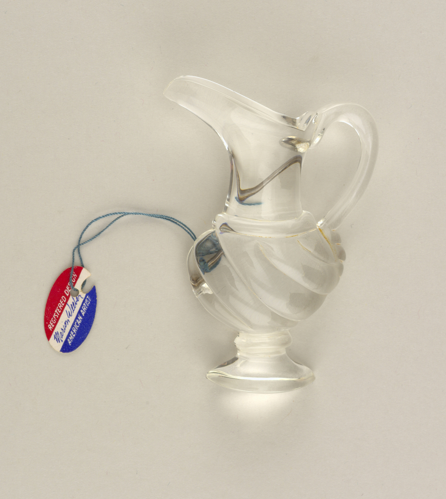 Clear brooch in the form of a footed pitcher or ewer.