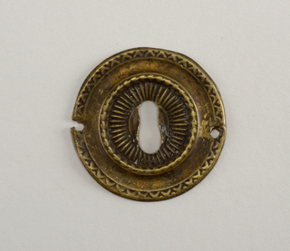 Circular. Repoussé decoration with raised boss at center. Foliate decoration at rim.