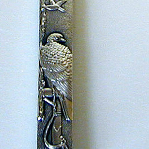 Knife in the form of a Japanese sword; handle with mottled surface, one side decorated with scene of a cat and a peony (?) with butterfly; other side depicts a hawk and other birds. Flat, curved blade engraved with stylized foliate decoration. Some guilding.