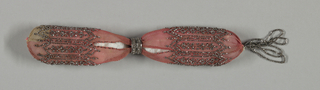 Pale red crocheted silk; cut steel beads form a symmetrical rectilinear repeating pattern.  Two steel rings control side closing; tassel of steel beads at one end.  Other tassel is missing.