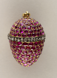 In the shape of an egg with red stones and a single dark band with clear stones in the middle with a clasp on the top.