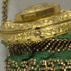 Very small round crocheted silk bag with gilt beads. Set in a gold rim with a lid, ornamented in relief of c-curves which opened shows star-shaped cover over shallow cavity.