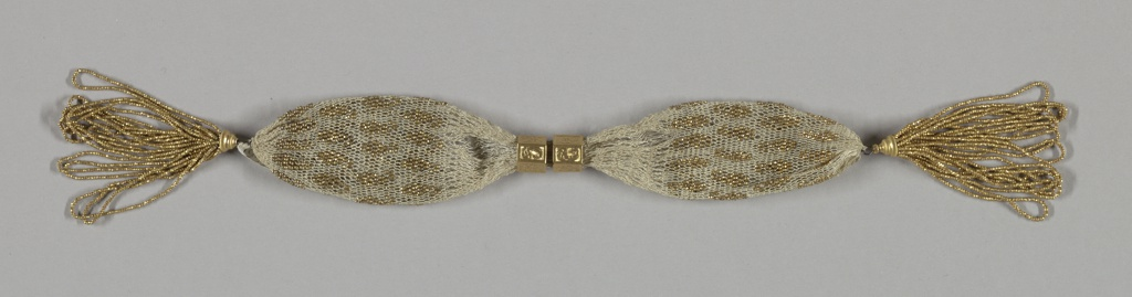 Netted white silk ornamented evenly with gold beads in small cone pattern.  Two hexagonal gold rings engraved with floral and scroll motifs, control a side opening.  Long tassels of gold beads at each end.
