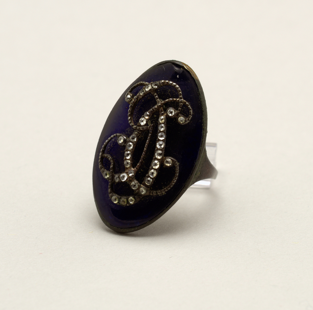 """B: Ring with large oval blue, paste or foil (?) stone on which are the initials """"G C D"""" in silver and paste diamonds."""