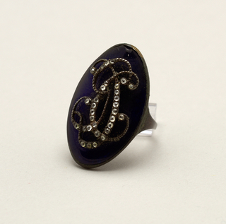 "B: Ring with large oval blue, paste or foil (?) stone on which are the initials ""G C D"" in silver and paste diamonds."