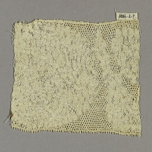 Straight-edged fragment with a Valenciennes ground in a large, solidly massed floral design.